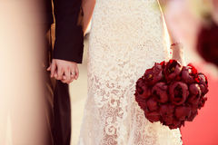 Beautiful bride and groom. Holding red flowers bouquet in hands Royalty Free Stock Image