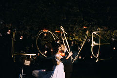 Beautiful bride and groom kissing in evening park under tree decorated with many lanterns. Lightpainted love word across the portr Royalty Free Stock Photo