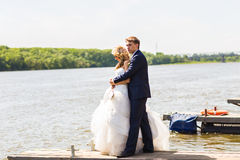 Beautiful bride and groom by a lake or river Stock Photos
