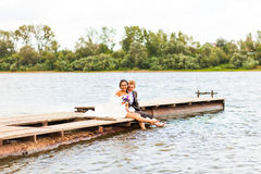Beautiful bride and groom by a lake or river Royalty Free Stock Image