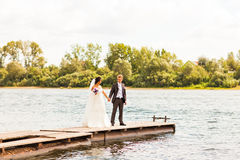Beautiful bride and groom by a lake or river Stock Photography