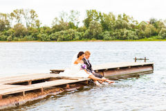 Beautiful bride and groom by a lake or river Royalty Free Stock Images