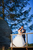Beautiful bride and groom leaning over the railing for a quiet m Stock Images