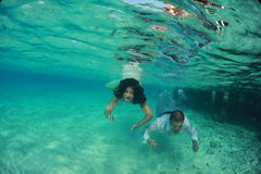 Beautiful bride and groom lovely kiss underwater Stock Photo