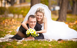 Beautiful bride and groom lying on grass and smiling at camera Royalty Free Stock Photos