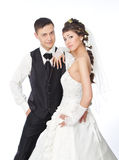 Beautiful bride and groom over white. Beautiful bride and groom standing at white background. Wedding couple fashion shoot Royalty Free Stock Image