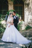 Beautiful bride and groom posing in a yard of a castle Stock Images