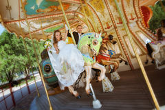 Beautiful bride and groom riding a carousel Stock Image