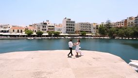 Beautiful bride and groom run towards each other along the beach stock video