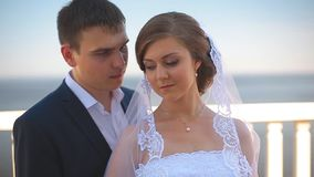 Beautiful bride and groom standing on a balcony overlooking the sea stock video footage