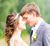 Beautiful bride and groom standing in grass and kissing. Wedding couple Stock Photography