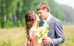 Beautiful bride and groom standing in grass and kissing. Wedding couple Royalty Free Stock Photography