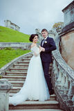 Beautiful bride and groom stay on stairs Stock Images