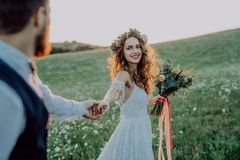 Beautiful bride and groom at sunset in green nature. Beautiful young bride and groom outside in green nature at romantic sunset, holding hands Royalty Free Stock Photos