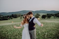 Beautiful bride and groom at sunset in green nature. Beautiful young bride and groom with sparklers hugging outside in green nature Royalty Free Stock Photos
