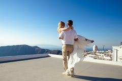 Beautiful bride and groom in their summer wedding day on greek island Santorini. Honeymoon story Stock Photography