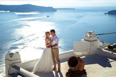 Beautiful bride and groom in their summer wedding day on greek island Santorini. Honeymoon story royalty free stock images