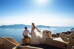Beautiful bride and groom in their summer wedding day on greek island Santorini. Honeymoon story stock image
