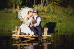 Beautiful bride and groom with umbrella on the bridge Stock Photo