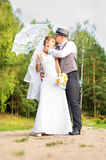 Beautiful bride and groom with umbrella Royalty Free Stock Photos