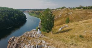 Beautiful Bride and groom wedding couple on a rock stock footage