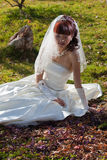 Beautiful bride on ground with autumn leaves Royalty Free Stock Photography