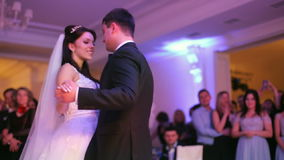 Beautiful bride and handsome groom dancing first dance at the wedding party. Confetti in the air. Very tender moment stock footage