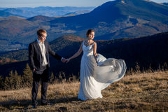 Beautiful bride and handsome groom holding hands on the mountain peak. Honeymoon.  Royalty Free Stock Image