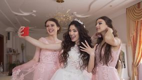 Beautiful bride is having fun with two bridesmaids. They are happily taking selfies on the mobile phone. Morning of the stock video