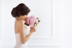 Beautiful bride with her flowers. Wedding hairstyle make-up luxury fashion dress and bouquet. Beautiful bride perfect style. Wedding hairstyle make-up luxury Royalty Free Stock Image