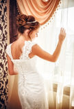 Beautiful bride in her wedding day. Beautiful bride in white wedding dress standing in her bedroom near the window Royalty Free Stock Photo