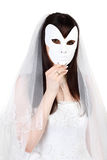 Beautiful bride hid face behind mask. Beautiful young bride hid her face behind white mask isolated on white background Stock Photos