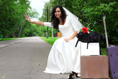 Beautiful bride hitch-hike Royalty Free Stock Photos
