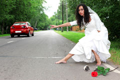 Beautiful bride hitch-hike Royalty Free Stock Image