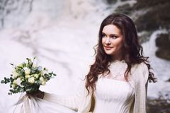 Beautiful bride holding a bouquet of flowers from roses on the background of a glacier. Beautiful attractive bride holding a bouquet of flowers from roses on the Royalty Free Stock Photography