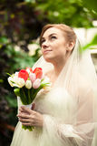 Beautiful bride holding bouquet at forest Royalty Free Stock Image
