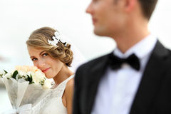 Beautiful bride holding a bouquet while looking to her groom Royalty Free Stock Image