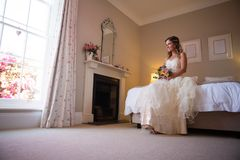 Beautiful bride holding bouquet while sitting on bed at home Royalty Free Stock Photo