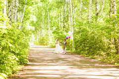 Beautiful bride holding bunch of balloons in the park. Couple of bride and groom with balloons. Newlyweds with balloons Royalty Free Stock Images