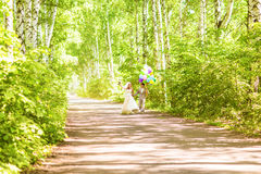 Beautiful bride holding bunch of balloons in the park. Couple of bride and groom with balloons. Newlyweds with balloons Stock Image