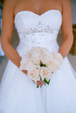 Beautiful bride holding a pink roses bridal bouquet. Vertical shot of a Caucasian white young woman holding a pink roses bouquet with both hands with focus on Stock Photos