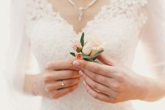 Beautiful bride holding stylish simple boutonniere in hands in b. Ackground of expensive silver necklace with pearls and wedding dress. bridal morning stock photos