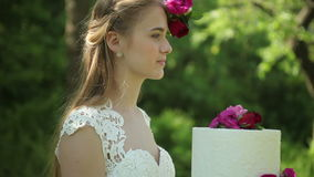 Beautiful bride holding a wedding cake with a flowers Outdoors stock video