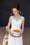 Beautiful bride holding a wedding cake and smiling. Vertical photo Stock Image