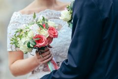 Beautiful bride is holding a wedding colorful bouquet. Beauty of colored flowers. Close-up bunch of florets. Bridal accessories. Female decoration for girl Royalty Free Stock Image