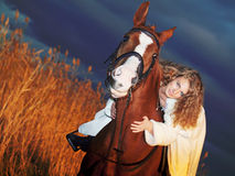 Beautiful bride  with horse in field at evening Royalty Free Stock Photos