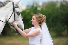 The beautiful bride with a horse in summer park Stock Photo