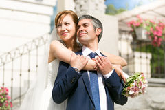 Beautiful bride hugging grooms shoulders on street at sunny day Stock Images