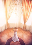Beautiful bride indoors. Beautiful bride in white wedding dress standing near the window indoors Stock Images