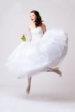 Beautiful bride jumping in studio Royalty Free Stock Images